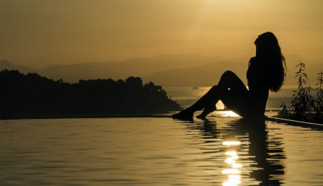 Girl sitting on the edge of a pool of one of the Corfu Luxury Private Villas during sunset.