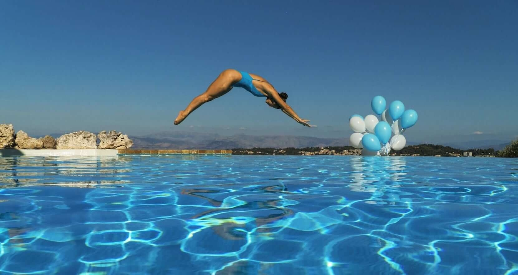 Girl diving into a swimming pool of one of the luxury villas in the Corfu Private Villas collection.